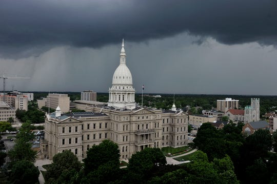 FILE - Storm clouds boil over Michigan's Capitol in Lansing (2014)