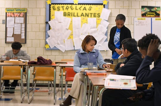 Bilingual history teacher Katherine Plaza works with students at Crosby High School in Waterbury, Conn.
