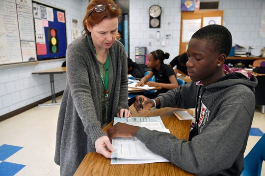 Crosby High School algebra teacher Jennifer Desiderio works with Lyndon Frederic, right, in her class in Waterbury, Conn.