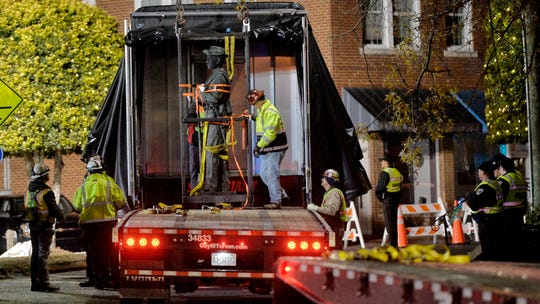 Workers load a Confederate statue onto a truck after it was removed from its spot in front of the historic Chatham County courthouse in Pittsboro, N.C. early Wednesday, Nov. 20, 2019.