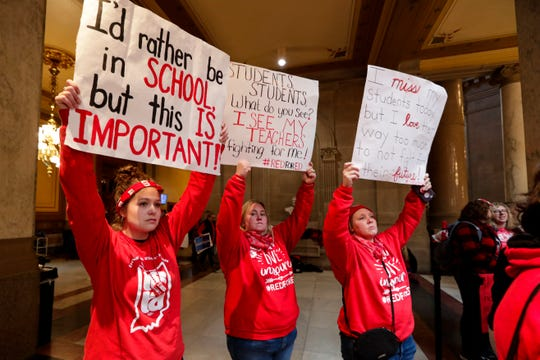 Indiana teachers wearing red have carry signs as they hold rally at the Statehouse in Indianapolis, Tuesday, Nov. 19, 2019, calling for further increasing teacher pay in the biggest such protest in the state amid a wave of educator activism across the country.