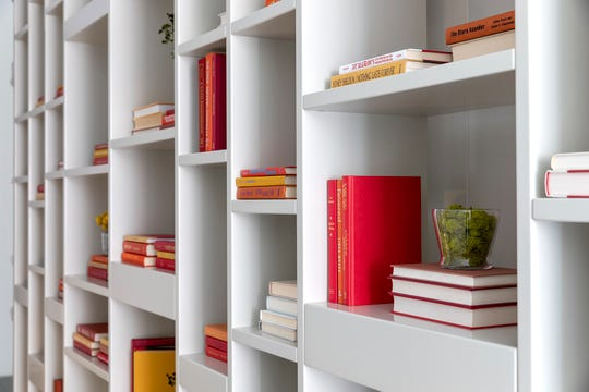 A mix of orange books adds color to an extensive bookcase. (Design Recipes/TNS)