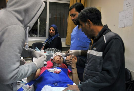 In this photo released by the Syrian official news agency SANA, a paramedic treats an injured woman wounded by Israeli missile strikes at a hospital in Damascus, Syria, Wednesday, Nov. 20, 2019.