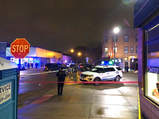 Chicago Police investigate the scene where an officer was shot by a suspected bank robber in the 4300 block of West Irving Park Road, Tuesday night, Nov. 19, 2019. A 15-year-old boy was also wounded in the shooting, while the suspect was shot and killed.