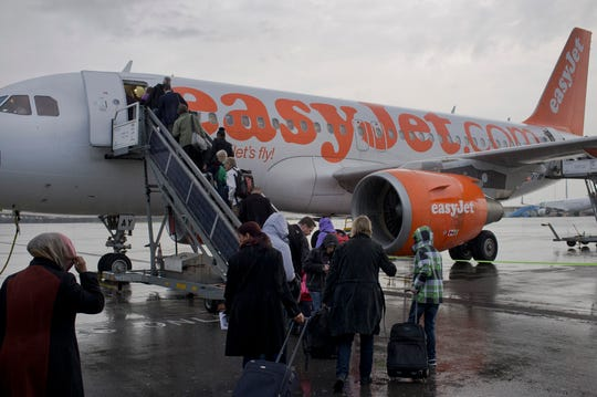 FILE - In this Thursday Oct. 18, 2012 file photo, passengers board a London-bound EasyJet flight at Amsterdam's Schiphol airport, Netherlands.