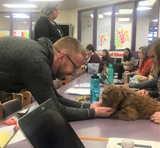 Rob Toepel, high school psychologist at Ripon Area School District, greets Shelby, a 12-week-old therapy puppy in training at the district's Journey Charter School.