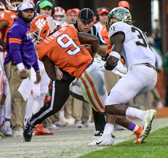 Clemson running back Travis Etienne (9) takes a pass from Trevor Lawrence near Wake Forest linebacker Ja'Cquez Williams(30) during the third quarter at Memorial Stadium in Clemson, South Carolina Saturday, November 16, 2019.