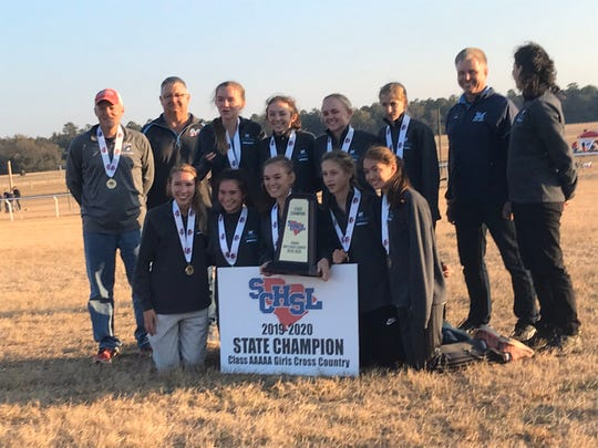 The J.L. Mann girls cross country team celebrates its Class AAAAA state title Tuesday in Camden