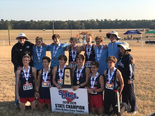 The Greer Middle College boys cross country team celebrates its state championship Tuesday in Camden