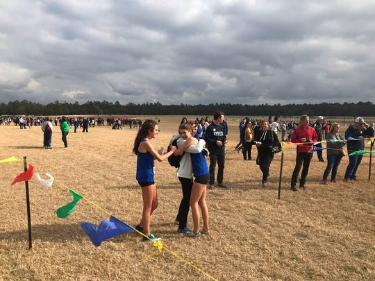 St. Joseph's Ava Dobson, left, and Caroline Linen celebrate finishing first and second at the South Carolina High School League state championship cross country meet Tuesday in Camden