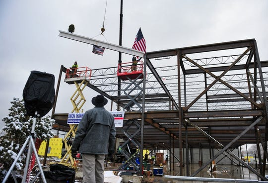 "The final structural beam is lowered into place on the new Longfellow Elementary School building during a ""topping out"" ceremony on Wednesday afternoon."