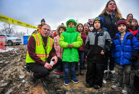 "Lance Boyd, principal of Longfellow Elementary School, watches Wednesday's ""topping out"" ceremony for the new Longfellow school buiding with his students. ""Topping out"" is milestone in construction projects where the final structural beam is secured into place signaling the start of the next phase of construction."