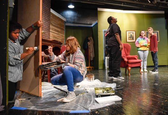 """Clide Jeannette, left, and Dawn Critser paint elements of the set while cast members, left to right, Jeremi Forte, playing Mr. Paravicini, Genesis Wilson playing Mollie Ralston and Landon Kahre playing Giles Ralston practice during a rehearsal of the Henderson County High School of Fine Arts production of Agatha Christie's play """"The Mousetrap"""" Tuesday evening. The murder mystery opened on London's West End in 1952 and has been running continuously since then making it the longest initial run of any play in history."""