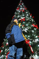 Matthew Albert, 10. Brownsburg, stands in front of the Christmas tree that he had the honor of flipping the switch on at Town Hall in Brownsburg on Dec. 4, 2010.