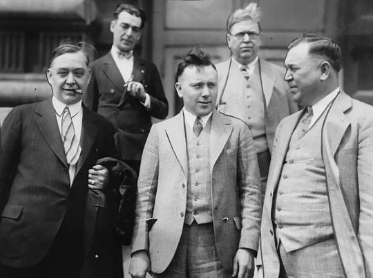 Indianapolis Mayor John Duvall (left front) was arrested May 17, 1927 with the City Controller William Buser after an eight month investigation into corrupt practices and making a false campaign financial statement. Front row, left to right: Mayor John Duvall, William Buser, City controller, and Claude Johnson, chief of police at the courthouse after his arrest.Back row: Arthur Reeves, Detective Sergeant and John Collins, city purchasing agent