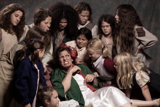 """Promotional photos for Courtesy of City Circle Acting Company's 2019 production of """"Annie."""" Pictured is Mary Denmead as Miss Hannigan surrounded by orphans played by McKenzie Vedepo, Shea Sanders, Chelsea Vedepo, Maya Hanna, Ana Rippentrop, Clara Visser, Maple Miller, Grace Bartlett, Rana Saba, Maddie Mitchell, Violet Whiting and Lily Vogts."""