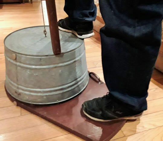 Attaching the washtub to a wooden platform with a half-inch gap allows the sound to resonate better, according to Driver, who applied engineering skill to the instrument. Performers place a foot on the tub's rim and rest their wrists on their knee as they pluck the string.