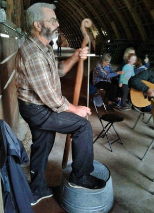 """In a dimly-lit livestock barn, Ric Driver of Iowa City plucks his washtub bass – sometimes called a """"gutbucket"""" – with a group jamming during the Fiddler's Picnic in September at the Johnson County Fairgrounds."""