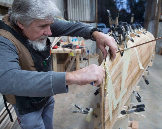 Ted Smith glues a wood panel to the canoe he is building in John Carter's Pearl River Canoe workshop at Morris Ice Company in Jackson, Miss. on Tuesday, Nov. 19, 2019.