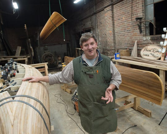 John Carter, craftsman, and owner of Pearl River Canoe, leans on a wooden canoe under construction in the workshop he conducts at the Morris Ice Company in downtown Jackson, Miss. on Tuesday, Nov. 19, 2019.