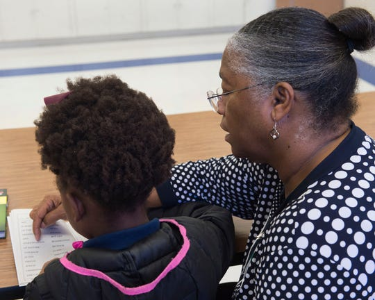Volunteer Cassandra Stovall reads with a student at Lake Elementary in Jackson, Miss., on Wednesday, Nov. 20, 2019. Stovall is a former librarian at the school and a longtime Girl Scout leader.