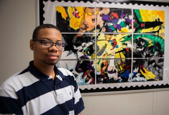 Kendarius Dupree has over 1,000 community service hours, which is more than the requirements for Jackson Central-Merry Early College High. He stands in front of a portrait he did.