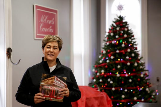 "Denise Bootsma, owner of McCord Candies, holds her book, ""Sweet Striped Delight,"" Wednesday, Nov. 20, 2019, in Lafayette."