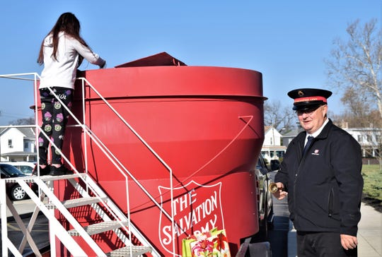 Salvation Army Volunteer Frank Spires rings a bell while a Mount Pleasant Elementary School student donates coins to the World's Largest Kettle Wednesday, Nov. 20. As part of the Salvation Army's fundraising efforts, the kettle made its way to several Lancaster schools to raise money to help families in need.
