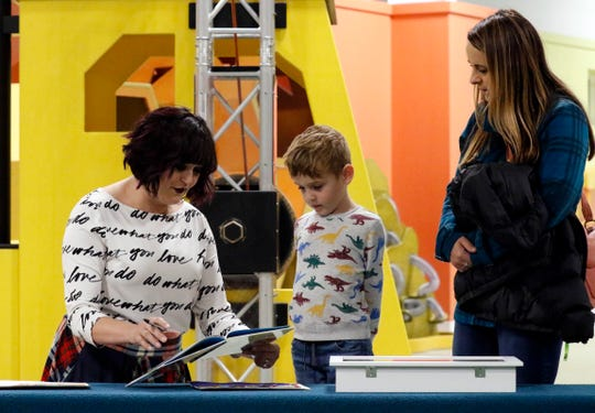 "Erin M. Burchwell, right, talks to Pierce Toler, 5, and his mother Jessie Hall as she signs a copy of ""Pip's Path Through Lancaster, Ohio"" during a launch for the children's book Tuesday night, Nov. 19, 2019, at AHA! Children's Museum in Lancaster. Burchwell wrote and illustrated the book which tells the story of a squirrel traveling through the city. Proceeds from the book's sale go to non-profits featured in it."