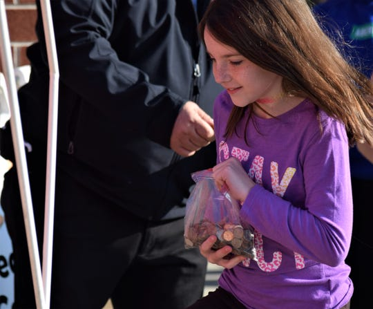 A Mount Pleasant Elementary school student clutches her bag of coins as she goes to donate them to the Salvation Army Wednesday, Nov. 20. The organization and the World's Largest Kettle traveled to Lancaster City Schools as part of a fundraiser for those in need in the community.