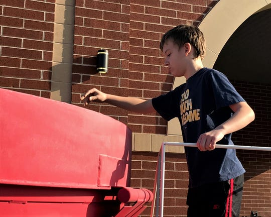 Chase Brown, a fourth grader at Mount Pleasant Elementary School, drops his coins into the World's Largest Kettle Wednesday, Nov. 20. As part of the Salvation Army's fundraising efforts, the kettle made its way to several Lancaster schools to raise money to help families in need.