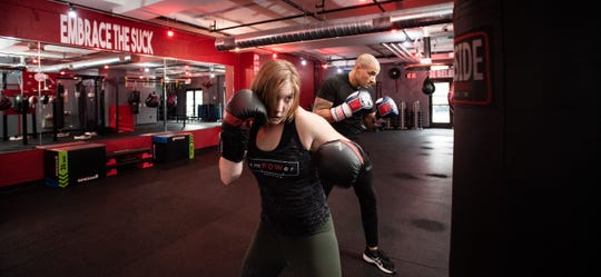 Leah Traciak-Zenker, 23, and Brian Daniels, 33, co-founders of emPOWer Lansing, demonstrate boxing techniques Tuesday, Nov. 19, 2019, at their boxing studio on East Michigan Avenue on Lansing's east side.