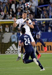 LA Galaxy forward Zlatan Ibrahimovic (9) head the ball in front of New England Revolution forward DeJuan Jones (24) in the first half at StubHub Center.