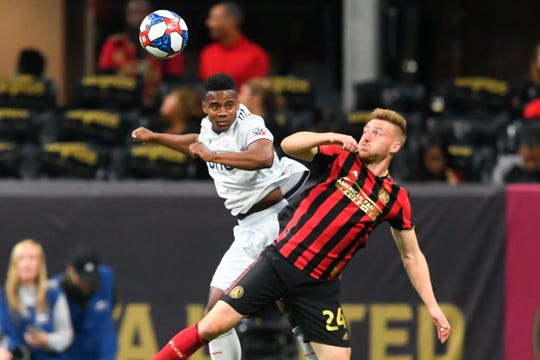 New England Revolution forward DeJuan Jones, left, and Atlanta United defender Julian Gressel battle for a header during the first half of round one in an MLS Cup playoff soccer game Saturday, Oct. 19, 2019, in Atlanta.