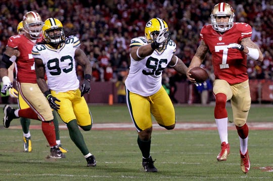 San Francisco 49ers quarterback Colin Kaepernick out runs Green Bay Packers Mike Neal (96) while running for a touchdown during the first quarter of  their divisional playoff game Saturday, January 12, 2013 at Candlestick Park in San Francisco, Calif.