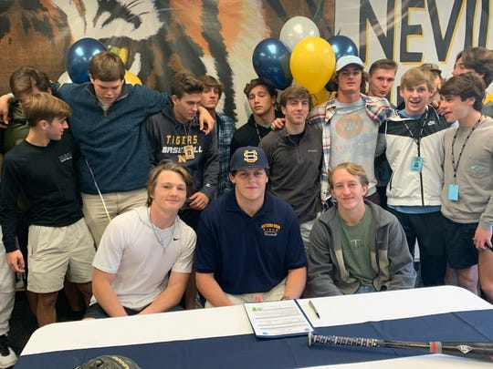 Parker Fugler (center) celebrates with his Neville teammates after signing with Southern Union Community College.