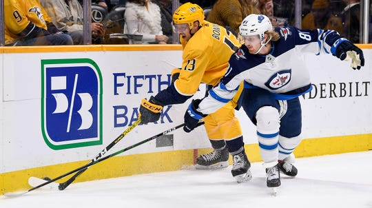 Nashville Predators center Nick Bonino (13) fights for the puck with Winnipeg Jets left wing Kyle Connor (81) during the first period at Bridgestone Arena in Nashville, Tenn., Tuesday, Nov. 19, 2019.