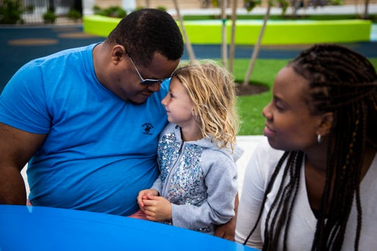 DeShannon Forbes leans his head against Madelyn Chase, 6, as he sits with his wife, Samantha Forbes, at Baker Park in Naples on Sunday, Nov. 17, 2019.