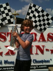 Estero resident Cody Krucker poses with the first racing trophy he ever won after winning a race in 2010 at the age of 5. Now 14, Krucker drives pro trucks and hopes to race in NASCAR someday.
