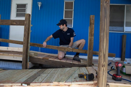 Brett Basford works on the railing section for Fred and JoAnn's new handicap ramp, Tuesday, Nov. 19, 2019, at the Finn residence in Bonita Springs.
