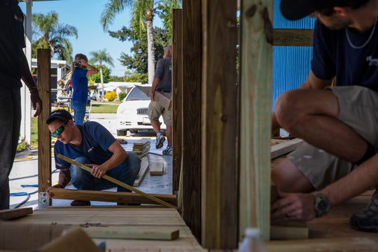 Volunteers help construct a handicap ramp for Fred and JoAnn Finn, Tuesday, Nov. 19, 2019, at the Finn residence in Bonita Springs.