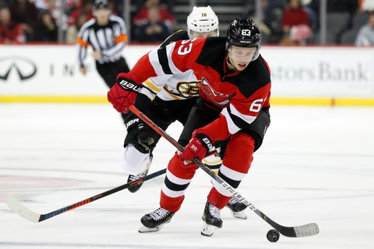 New Jersey Devils left wing Jesper Bratt (63) skates with Boston Bruins right wing Brett Ritchie (18) in pursuit during the second period of an NHL hockey game Tuesday, Nov. 19, 2019, in Newark, N.J.