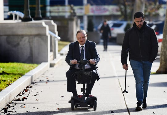 James Demetrakis, big-time developer, who will be   sentenced for an insider loan scam at U.S District Court in Newark, rides on a power wheelchair accompanied by an unidentified man an enroute to the court Wednesday morning on 11/20/19.