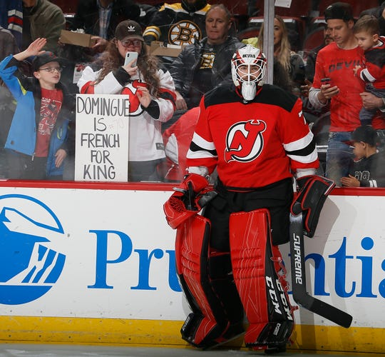 Fans hold signs and watch goalie Louis Domingue #70 of the New Jersey Devils, who was called up from Binghamton today, during warmups before an NHL hockey game against the Boston Bruins on November 19, 2019 at the Prudential Center in Newark, New Jersey.