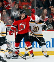 Blake Coleman #20 of the New Jersey Devils knocks down a shot from the point in front of the Bruins net as Urho Vaakanainen #58 of the Boston Bruins defends in the first period of an NHL hockey game  on November 19, 2019 at the Prudential Center in Newark, New Jersey.
