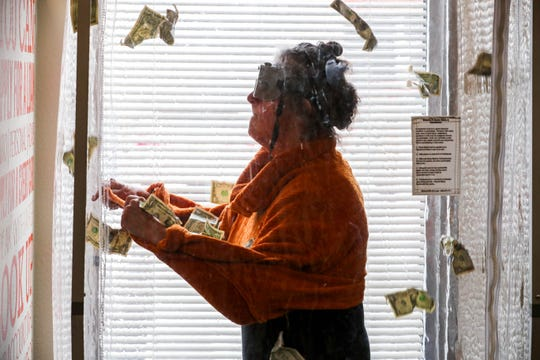 Maria Chavez wins a chance to grab cash in a wind tunnel at the First Financial Credit Union in Las Cruces on Wednesday, Nov. 20, 2019.