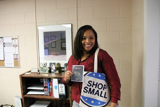 Alamogordo Chamber of Commerce Marketing Communications Coordinator Brittani Gandy holds up an Alamogordo Small Business Saturday Passport.