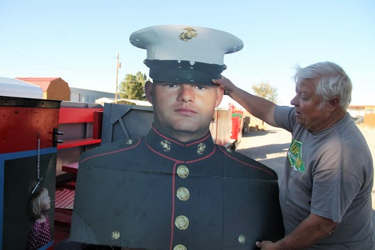 Wally Anderson of Alamogordo Toys for Tots holds up a cardboard cutout of local Marine Kody Mallett.