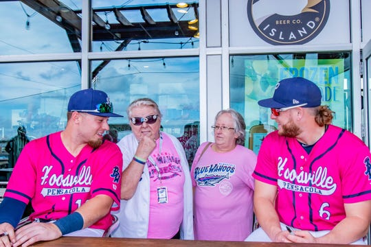 Ryan Costello (left) and Travis Blankenhorn (right) are pictured with Pensacola Blue Wahoos' employees in an undated photo. Costello unexpectedly passed away earlier this week.