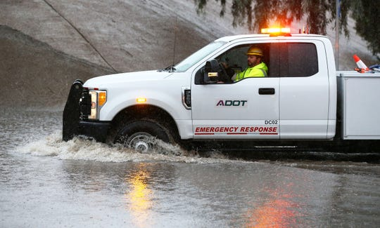 An ADOT truck drives through floodwaters that stranded several cars on Greenway Road at the Interstate 17 underpass on Nov. 20, 2019, in Phoenix.